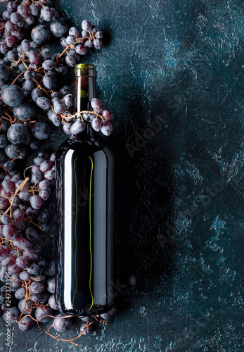 Bottle of red wine and grapes.