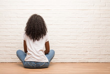 Young Black Woman Sitting On Wooden Floor Showing Back, Posing And Waiting, Looking Back