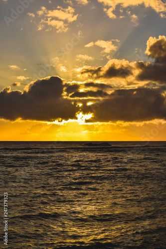 Sunset clouds and bright light rays over Pacific Ocean