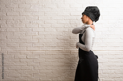 Young baker indian woman against a bricks wall with back pain due to work stress Canvas Print