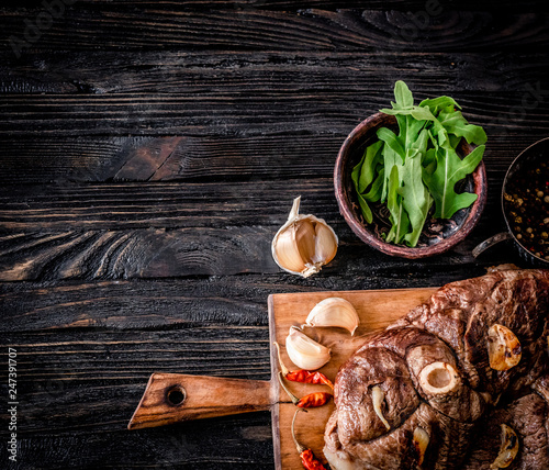 Grilled lamb meat with garlic on a wooden board, top view