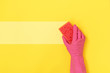 Leinwanddruck Bild - Woman holding sponge for washing in her hands against yellow background