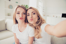 Close Up Photo Of Two People Pretty Mum Mommy And Teen Daughter Video Call Millennials Trendy Make Take Selfies Duck Lips Fooling Wear White T-shirts Jeans Sit On Comfy Sofa Couch