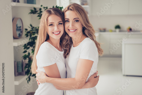 Close up photo cheer toothy smiling two people mum and teen daughter holding hands arms around chest lovely looking best buddies rejoice wear white t-shirts jeans in bright kitchen