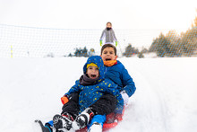 Children Playing With A Sled On The Snow