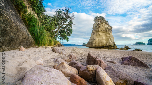 sandstone rock monolith behind stones in the sand at cathedral cove, new zealand 6