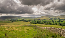 Storm Clouds Gathering Over A Valley Of Farm Land In Yorkshire, England. Handmade Stone Wall. Sheep Grazing.