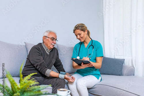 Fototapeta Nurse Visiting Senior man For Check Up. Young nurse measuring blood pressure of elderly man at home. Happy senior man having her blood pressure measured in a nursing home by her caregiver obraz na płótnie