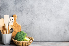 Kitchen Shelf On Gray Concrete Background. Zero Waste House. Ceramic Glass, Wooden Kitchen Appliances, Wicker Basket With Broccoli. Copy Space.