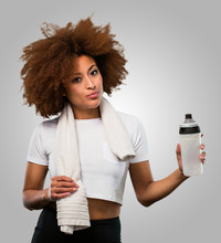 Young Fitness Afro Woman Holding A Water Bottle And A Towel