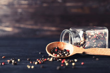 Black Pepper With Spoon And Glass Jar On Black Wooden Table