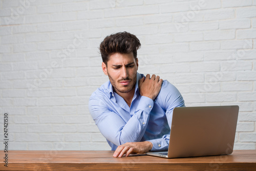 Young business man sitting and working on a laptop with back pain due to work st Canvas Print