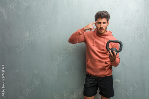 Leinwand Poster Young fitness man against a grunge wall man making a concentration gesture, looking straight ahead focused on a goal