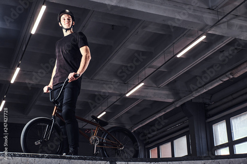 Professional BMX rider in protective helmet getting ready to jump in a skatepark Wallpaper Mural
