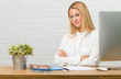 Portrait of young student sitting on her desk doing tasks crossing his arms, smiling and happy, being confident and friendly