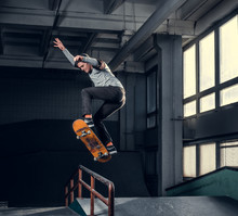Skateboarder Performing A Trick On Mini Ramp At Skate Park Indoor.