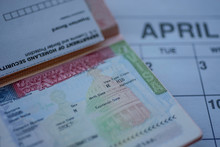 H1B Visa (for Specialty Workers) Stamp In Passport, Blurred April Calendar On Background. H1B Visa Program Deadline Concept. Close Up View.