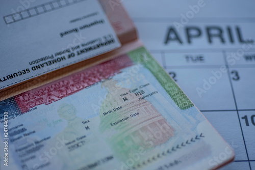 H1B visa (for specialty workers) stamp in passport, blurred april calendar on background Fototapet