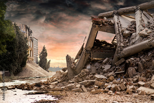 Photo View on a collapsed concrete industrial building with dark red dramatic sky above