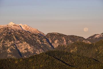 Fototapetafull moon sets behind mountains at Berchtesgaden alps, Bavaria