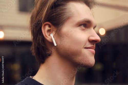 Man in wireless headphones outdoor, street, restaurant Canvas Print