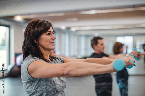 Fotografia Group of cheerful seniors in gym doing exercise with dumbbells.