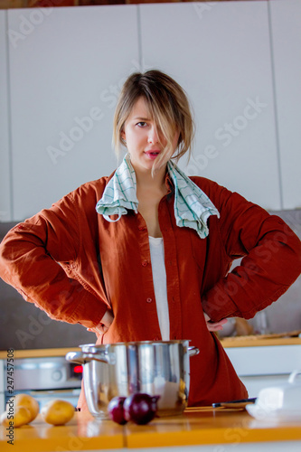 Beautiful tired housewife with pot cooking on kitchen.