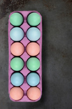 A Dozen Egg Carton Of Six Pastel Dyed Eggs With On A Metal Baking Sheet Surface.