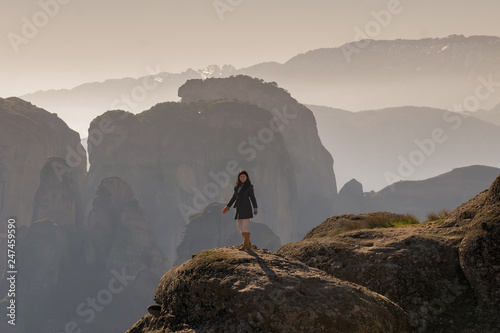 Woman standing on the historic rocks of Meteora in Greece.