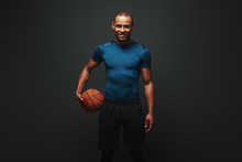 He Is A New Champion. Handsome Sportsman Standing Over Dark Background With Basketball Ball In His Hand