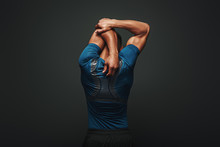 Even If You Don't Have Time For A Big Workout, Stretching In The Morning And Night Really Changes Your Body. Sportsman Is Stretching Standing Over Dark Background