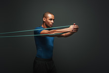 Get Stronger Every Day. Sportsman Working Out With Resistance Band Over Dark Background