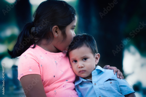 Fotografie, Obraz  An emotionally hurt young boy leaning on her older sister and being comforted by her kiss and support
