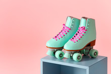 Pair Of Vintage Roller Skates On Storage Cube Against Color Background. Space For Text