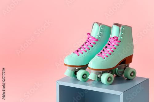 Fotografia  Pair of vintage roller skates on storage cube against color background