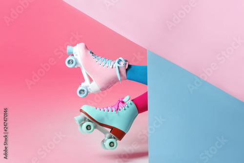 Photographie Woman with vintage roller skates on color background, closeup