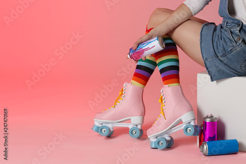 Woman with vintage roller skates and spray paint cans on color background, closeup. Space for text