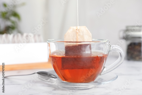 Brewing tea with bag in cup on table
