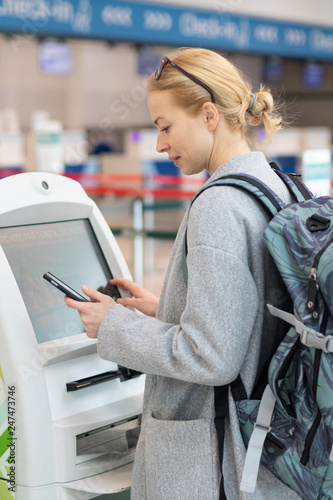 Staande foto Hoogte schaal Casual caucasian woman using smart phone application and check-in machine at the airport getting the boarding pass. Modern technology on airport.
