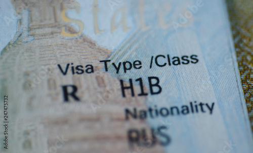 Fragment of H1B visa (for specialty workers) stamp in passport, blurred april calendar on background Canvas Print