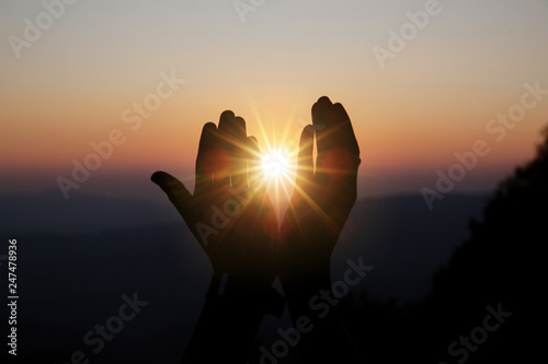 Photo Faith of christian concept: Spiritual prayer hands over sun shine with blurred b
