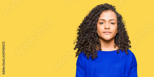 Fotografiet  Young beautiful woman with curly hair wearing winter sweater Relaxed with serious expression on face
