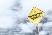 Winter Storm Warning Sign With Snowfall And Stormy Background