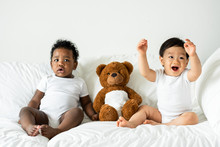 Babies And A Teddy Bear On The Bed
