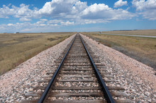 Train Tracks On An Open Plain Stretching Out To A Blue Sky And Clouds On The Horizon