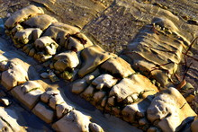 Diagonal Weathered And Sea Washed Rocks At The Shore Line, With Crystal Clear Sea Water, Sparkling In The Sunlight