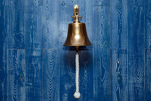 Copper Old Vintage Bell, Doorbell, Rope On A Wooden Blue Aged Wall. Concept Decor Element In Interior Of Deck, Cabin Of Ship, Restaurant, Room, House Decorated On Marine Theme