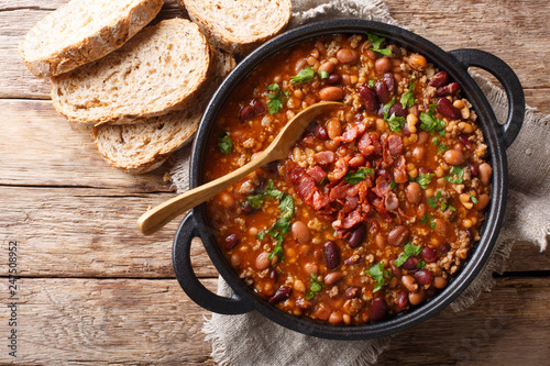 Delicious cowboy stew of beans with ground beef, bacon in a spicy sauce closeup in a bowl. horizontal top view