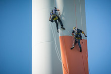 Inspection Engineers Abseiling Down A Rotor Blade Of A Wind Turbine In A North German Wind Farm On A Clear Day With Blue Sky