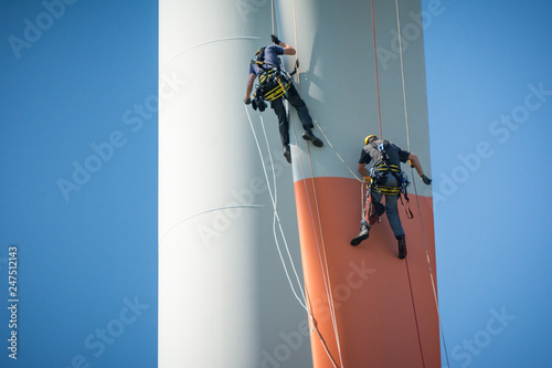Inspection engineers abseiling down a rotor blade of a wind turbine in a North G Wallpaper Mural